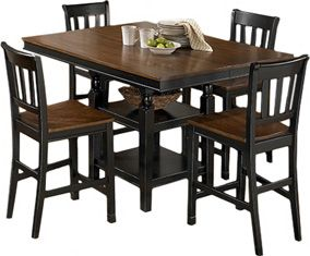 Ashley Owingsville SQ DRM CTR EXT Table and Four Barstools - The rich cottage beauty of the Owingsville dining collection uses a rich medium brown finish on chair seats and table tops contrasting the painted black color of the table base and chair legs to create a stylish two-tone cottage look that is sure to add a warm inviting atmosphere to any dining area.