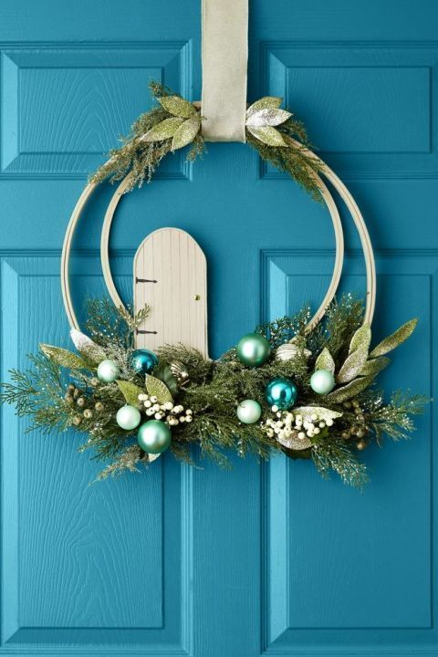 """Greet guests with magical decor! Nest a 14"""" embroidery hoop inside an 18"""" one and attach with strong tape at the clasps. Cover the tape with a loop of wide ribbon (you'll use it for hanging later). Secure faux greenery, white berries and glittery ornaments along the bottom of the hoops with thin green floral wire. Create the fairy door from an 8"""" x 4"""" piece of balsa wood: First, trace an upside-down cereal bowl to make a rounded top, cut out with scissors, and use a brown pen and a ruler to…"""