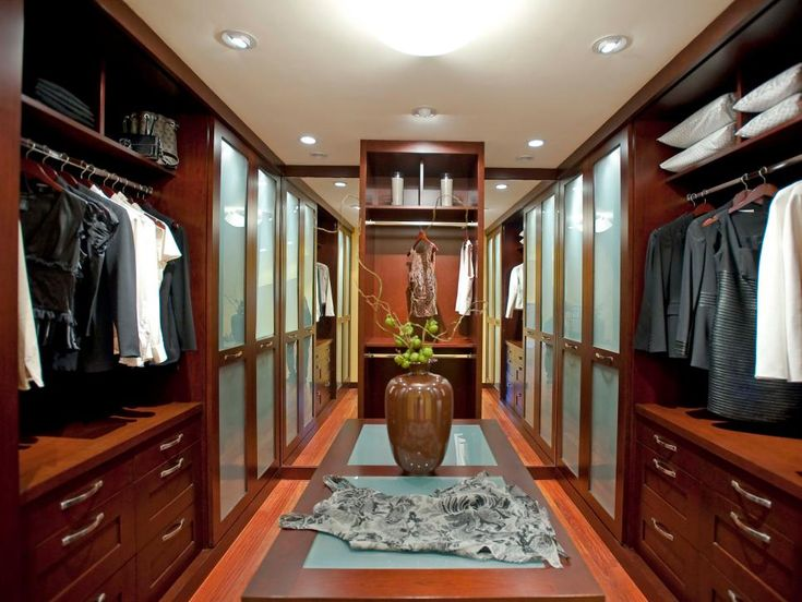 finding the perfect outfit is easy in this gorgeous walk in designer closet complete with folding table and storage drawers