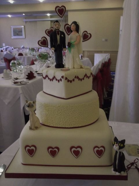 A deep red and ivory cake with hearts running throughout the design.