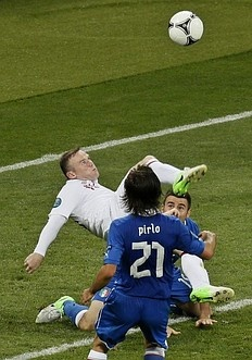 England's Wayne Rooney is flanked by Italy's Andrea Pirlo, left, and Andrea Barzagli as he performs a bicycle kick during the Euro 2012 soccer championship quarterfinal match between England and Italy in Kiev, Ukraine, Sunday, June 24, 2012.