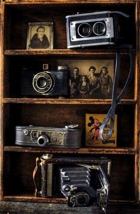 Heel gaaf hoe de oude kast dient als houder voor de oude foto's en oude camera's