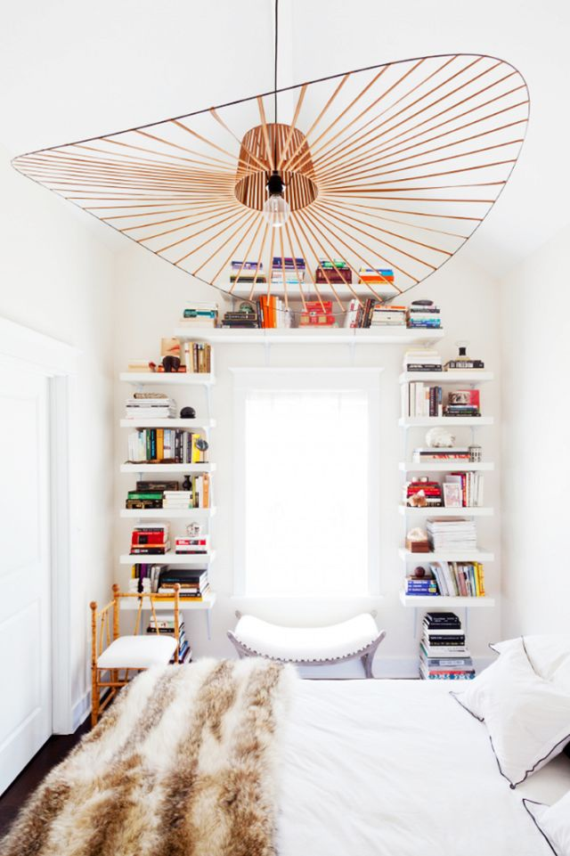 Small bedroom with a wall of floating shelves stacked with books, a bench below the window, and a pendant light above the bed