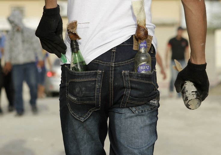 A Bahraini anti-government protester adds a lighter to his back pocket as he heads into clashes with riot police toting petrol bombs Monday, April 2, 2012,