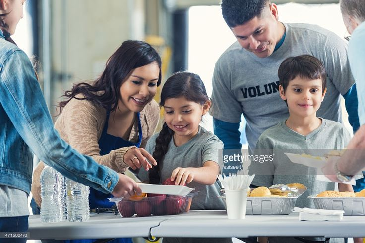 Stock Photo : Family serving meals while they volunteer in soup kitchen together