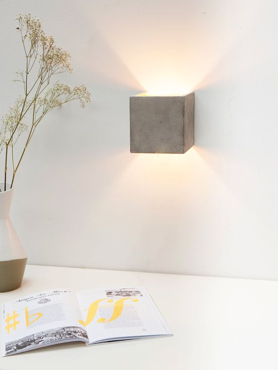[ B3 ] Cubic wall lamp [ B3 ] is cast from gray concrete . It combines noble gold with rough concrete into a timeless and elegant designer lamp .