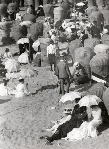 Strandleven 1908, plaats onbekend. De dames in lange jurken en parasols, en de heren met vilthoeden en in kostuum. (zie ook de vele rieten strandstoelen).