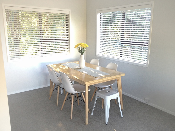 New dining room setup with plywood table, eames chairs and metal end stools