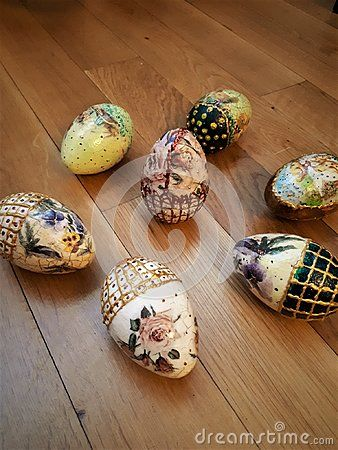 Happy eggs on wood, are painted in vibrant colors: yellow, gold, copper, red, green, silver. Eggs have different patterns lance, pansies, roses, rabbits.