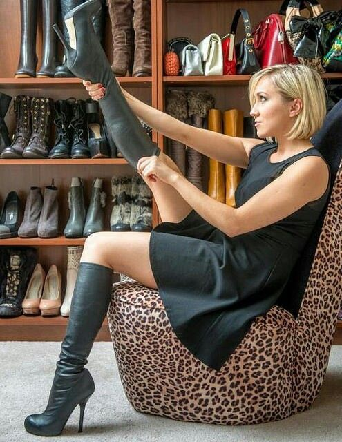 Blonde in black dress pulling on boots in front of boot collection #highheelbootsknee