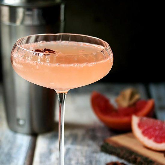 A grapefruit martini made with grapefruit juice, ginger infused simple syrup, lime juice, grated ginger, star anise, and rhubarb bitters.