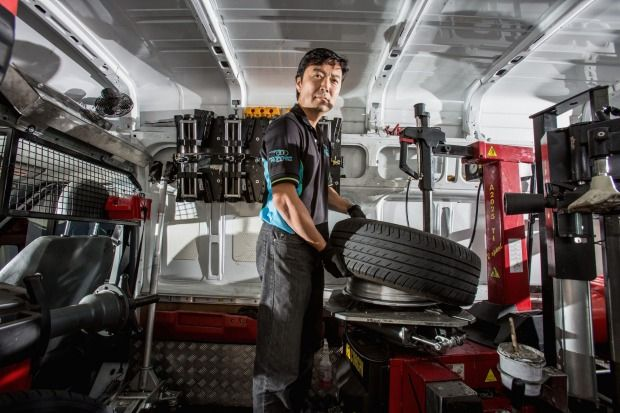 John Shim fits a tyre in the mobile Road Runner mobile workshop.