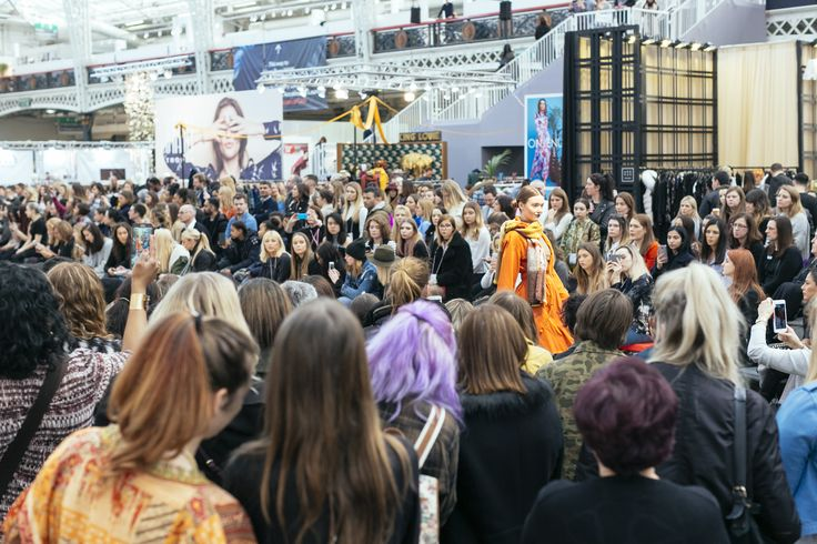 Huge crowds gathered to watch the fashion shows, across both the Main Stage and Spirit Stage catwalks. Here one model walks the runway showcasing an orange coat and scarf, as the audience watch on and capture the look on their phones and cameras.