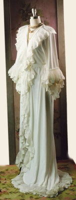 Christine's Dressing Gown. Inspired by the ruffled robe worn by the beautiful songstress during the hauntingly romantic dressing room scene in which his voice comes to her. Long bridal train extends behind while tiers of assorted lace patterns cascade coquettishly from a velour velvet sashed robe.