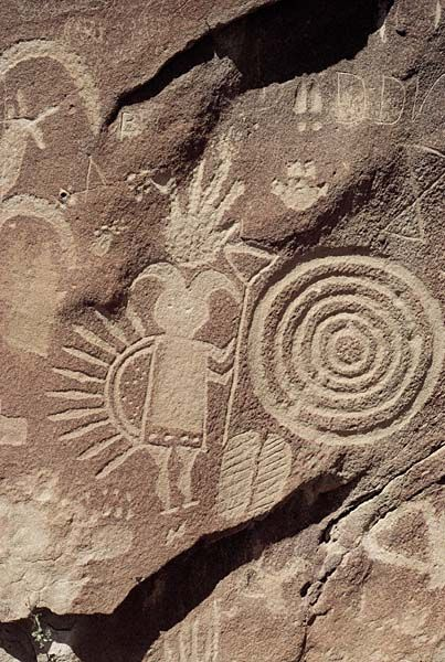 Navajo Petroglyphs at Crow Canyon.Detail of pictograph panel, Crow Canyon. Navajo people interpret this as a representation of Gháá' ask'idii. His horns tie him to the Mountain Sheep People, an ancient race associated with the night chant, Tl'eejí. Generally a benevolent figure, Gháá' ask'idii carries many kinds of seeds and foods in his feather-crowned backpack.Photograph by James Matthew Copeland, via New Mexico Bureau of Land Management.