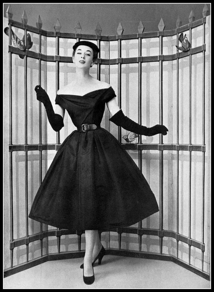 Elinor in charming black faille dinner/cocktail dress, full skirt, off-shoulder bateau neckline, cinched at waist with black leather belt, by Christian Dior, photo by Pottier, 1954