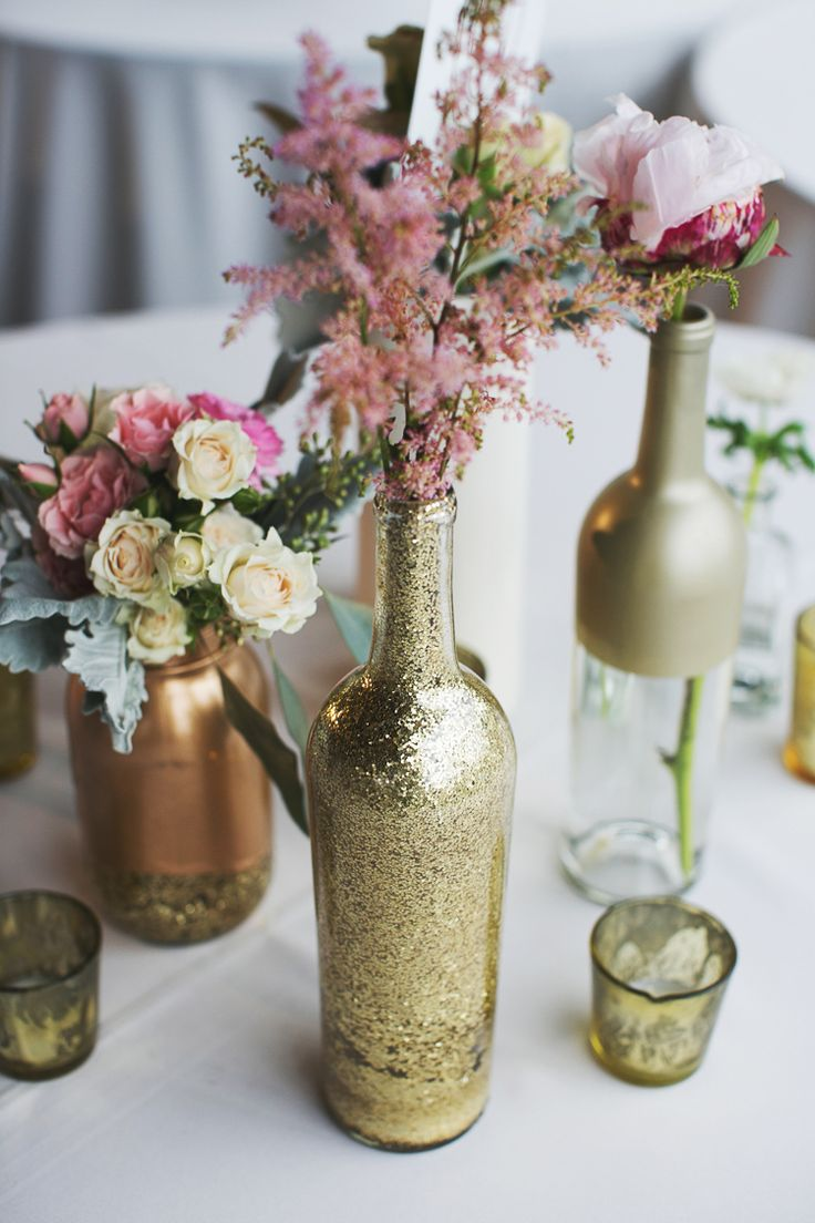 No glitter and spray pewter instead of gold but love the different paint options on these bottles. Adds visual interest. Easy DIY. {Photo by EE Photography via Project Wedding}