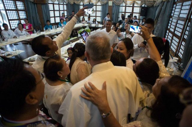 PRIVATE MEETING. In this behind-the-scenes meeting, Pope Francis poses for 'selfies' with survivors of Super Typhoon Yolanda (Haiyan) on January 17, 2015, as part of his trip to the Philippines. Photo by Osservatore Romano/AFP