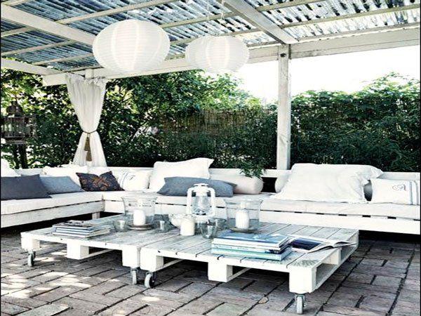 Ambiance détente sous la pergola avec ce salon de jardin blanc fabriqué en palette avec banquette d'angle et table basse mobile