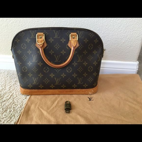 Louis Vuitton Alma bag This LV bag was purchased second hand. I had it authenticated myself after purchasing it ( picture 4). It is a beautiful purse in good condition. It is clean, but does show signs of wear on the leather. It comes with the lock and key as well as a dust bag. Louis Vuitton Bags Satchels