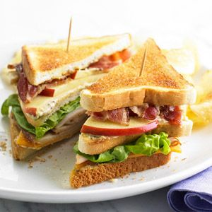 To make Turkey, Bacon & Apple Club, in a bowl combine mayonnaise, Dijon mustard, snipped fresh thyme leaves; spread on three slices of bread. On one slice layer cheddar cheese, sliced turkey, and lettuce. Top with another slice of bread, spread side up, then layer bacon and apple. Top with the remaining bread slice, spread side down. Skewer with long picks and cut in half to serve. Chips are optional, but highly recommended. Makes 4 sandwiches (8 servings).