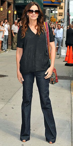 JULIA ROBERTS  blousy black top and flare J Brand jeans accessorized with movie star shades and an ethnic printed purse