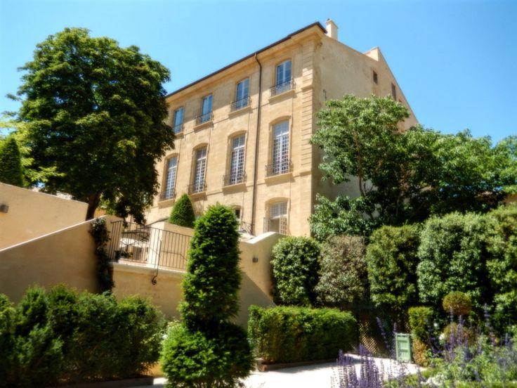 Façade ocre, côté jardin, en pierres de Rognes de l'Hôtel particulier de Caumont dans le quartier Mazarin d'Aix-en-Provence, avec un magnifique tilleul en fleurs.
