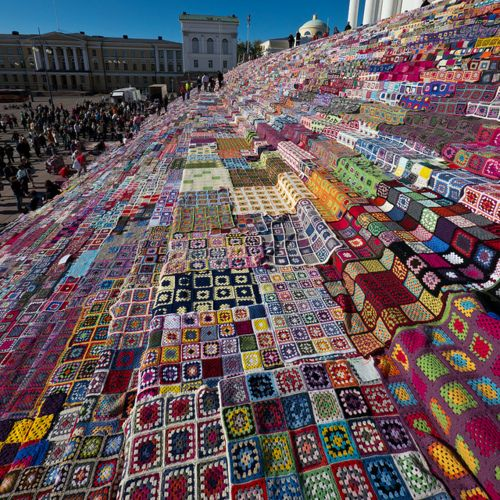 Stairs of the Helsinki Cathedral filled with crocheted patchwork quilts of the world.