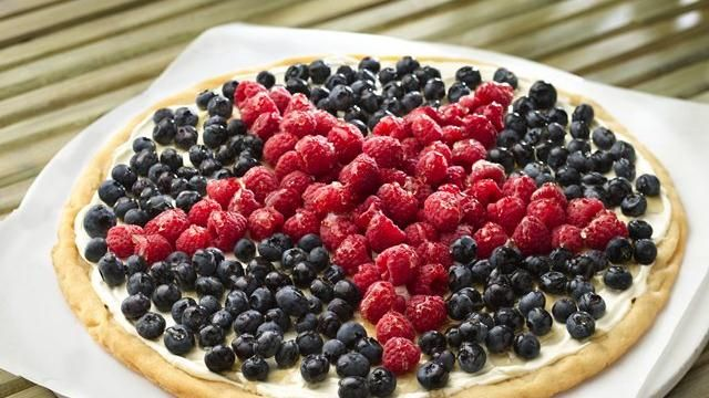 Easy Patriotic Cookie Pizza with store bought sugar cookie dough, cream cheese and fruit.