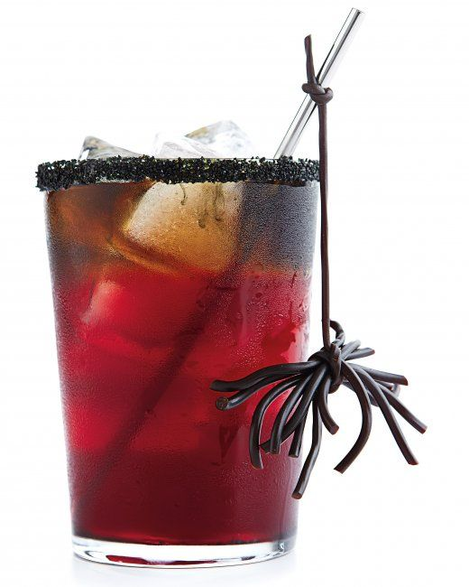 Creepy Cocktail -      Black sanding sugar -      1 lime wedge -      Ice -     1 tablespoon fresh lime juice -      1 ounce light rum -      3 tablespoons simple syrup -      1/4 cup 100 percent pomegranate juice -      1 ounce dark rum -      Licorice spider, for garnish