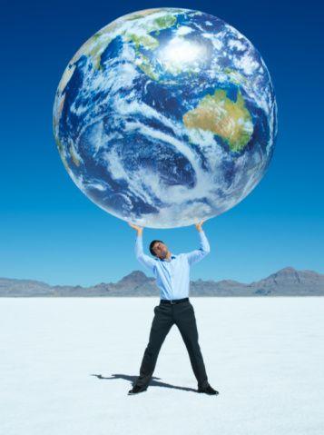 Man Holding Up Globe In Desert Stock Photo 82834139