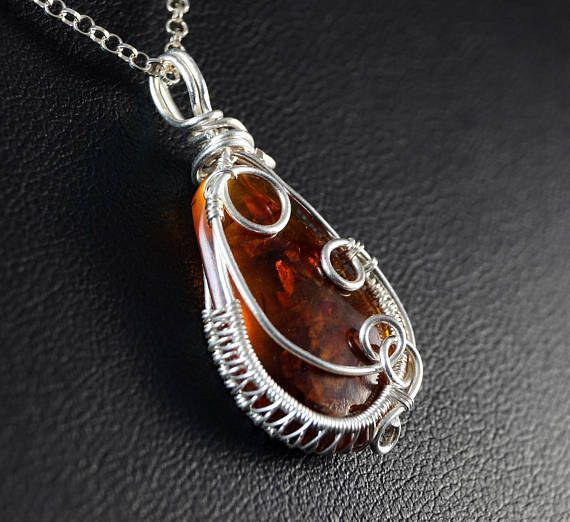 A delicate, unique, handmade, wire wrapped pendant with Baltic amber Pendant was designed and made by Me, using an extremely labor-intensive and precise wire-wrapping technique, with silver 925, 930 and 999. Silver strongly oxidized and polished to emphasize the braid tangles.