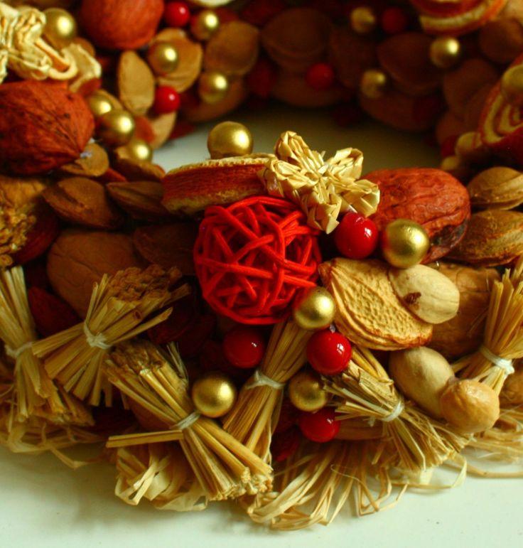 Vítací věnec 3 Ozdobný věnec z tónovaných přírodních materiálů s náznakem přicházejících vánoc. Je vyroben ze skořápek oříšků, pecek, trávy, slámy, sušených pomerančů, pomerančové kůry, šustí, lýka. Dozdoben je přízdobami Upevněn je na pevném slaměném korpusu. Korpus je obalen přírodním papírem. Ze zadní strany je poutko na zavěšení. Na dveře se ...