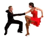 Dancers : Young ballroom dancers in formal costumes posing against a solid background in a studio