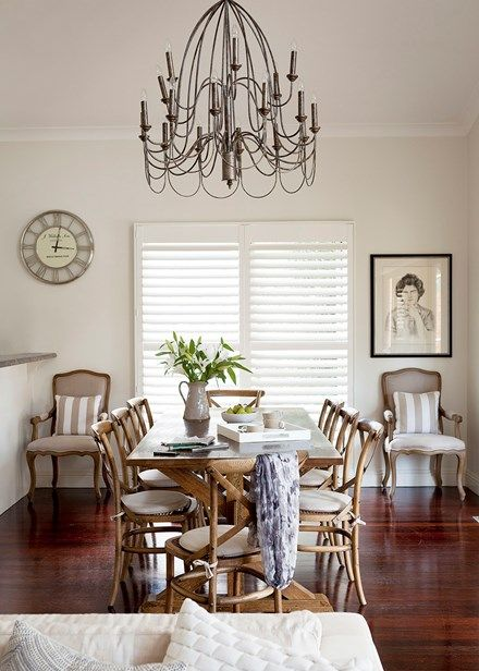 Home from the Hamptons - Dining room Dinnertime is a chic and easy affair thanks to a wooden dining setting from Town and Country Style. The eye-catching chandelier is from One World Collection, while the 'Provence' armchairs were found at Town and Country Style. Plantation shutters from Mirage Interiors complete the pared-back scheme.