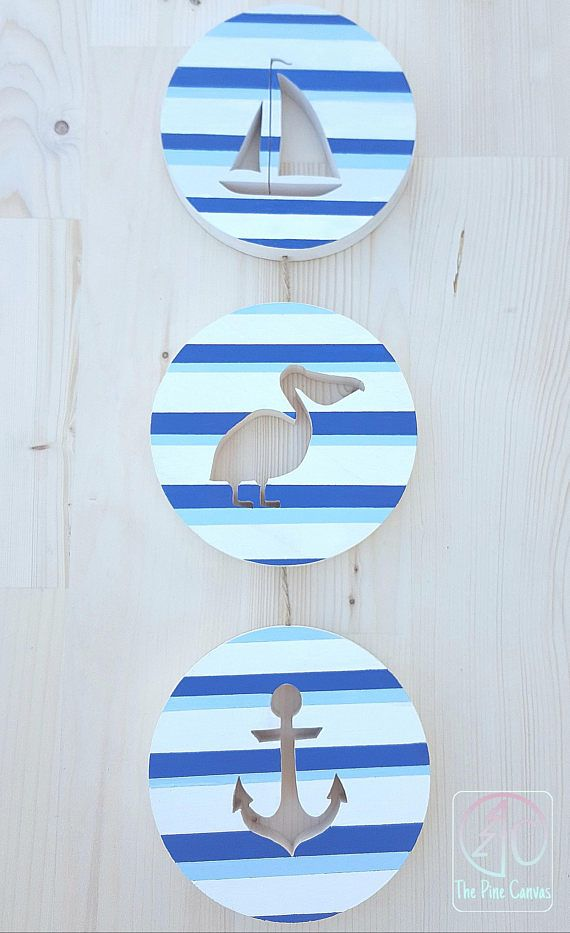 Three Piece Pelican Wall art- Repin for great gift ideas!  This Nautical Wall Art will make a great gift for a new home owner to hang in a hall or entryway. Great on narrow walls.   This Nautical Decor features a sailboat, pelican and anchor silhouette on dark blue, light blue and white striped circle of pine.   The cut out in the centers show your wall color through making every piece unique to your room design.