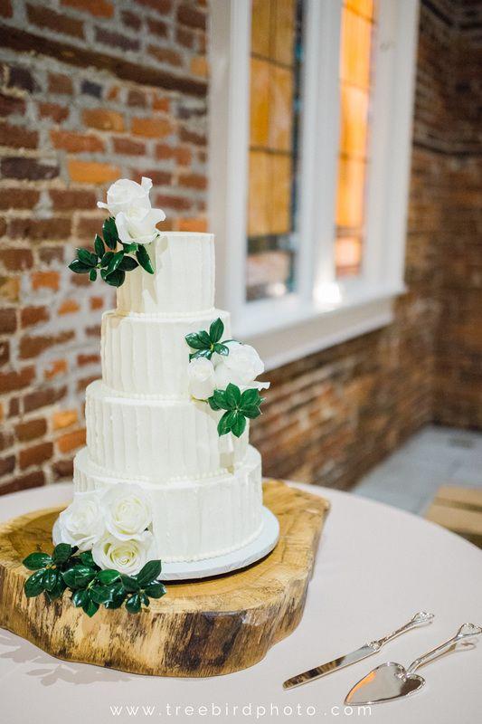 White Cake l Cake Flowers l Greenery l Cake Knife & Server l Silver l Glass l Wooden Cake Stand l Saint Thomas Preservation Hall l Wilmington, NC l Wedding l Knot Too Shabby Events