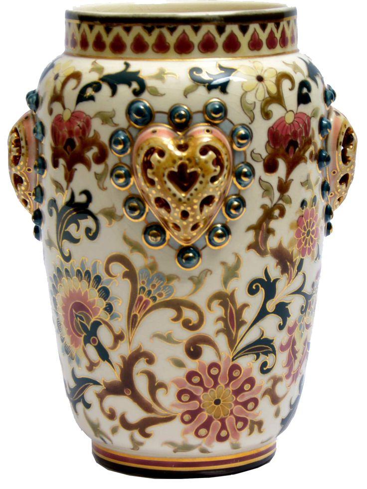 Zsolnay díszváza Áttört, plasztikus elemekkel díszített  porcelánfajansz. Felületén magas tüzű,  színes mázakkal festett és aranyozott  perzsa virágdekor.  Alján jelzett: masszába nyomott Zsolnay,  Pécs és 1666 (formaszám), valamint máz alatt kékkel bélyegzett családi jegy. Zsolnay, Pécs, 1880 körül Magassága: 21 cm Zs16/83e