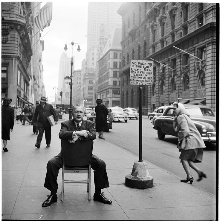 """New York: World Art Center [Artist sitting on a chair on the sidewalk.]"""