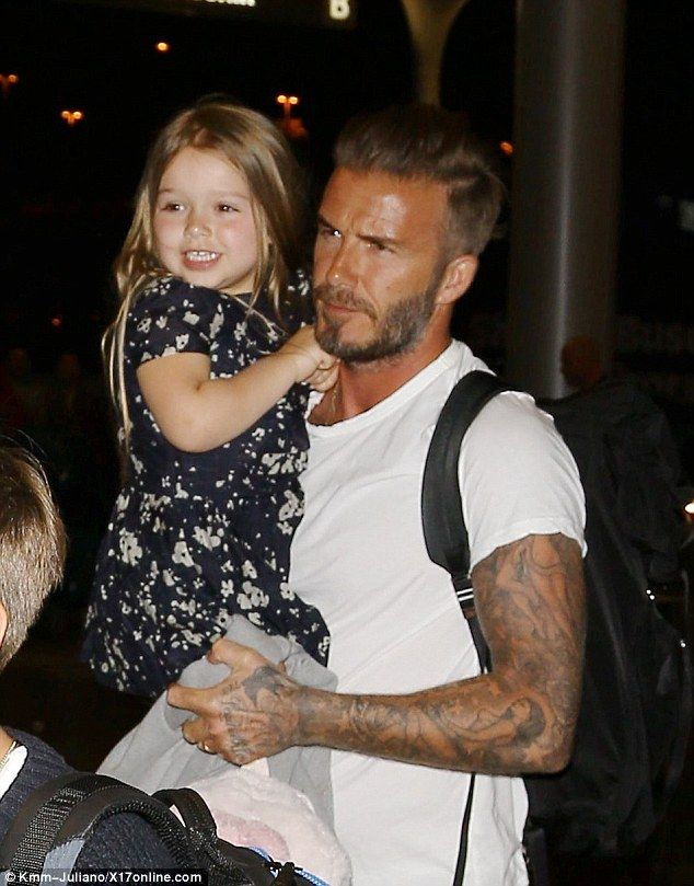 Sunkissed: David Beckham arrived at Los Angeles International airport on Sunday without wi...