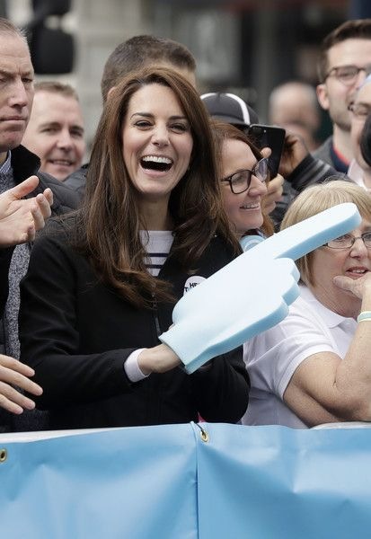 Catherine, Duchess of Cambridge laughs as she wears a big foam hand passed to her to put on by Prince Harry as they cheer on runners at a 'Heads Together' cheering point along the route of The Virgin Money London Marathon 2017 on April 23, 2017 in London.