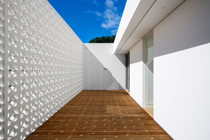 The screen wall, which is constructed out of precast concrete breeze blocks, ensures privacy on an upstairs patio, finished with garapa decking.
