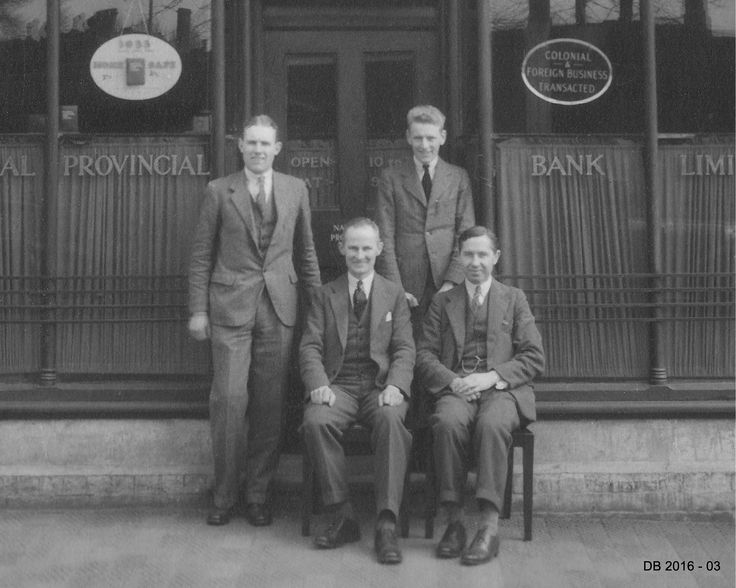 The manager and his staff outside the National Provincial Bank, Stafford Road Cannock in 1933, The sign proclaims 'Colonial and Foreign Business Transacted' and the ad in the window is for small home safes.