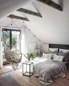 chambre a coucher sous les combles, sol en bois clair, chaise bercante, grandes fenetre vers le balcon