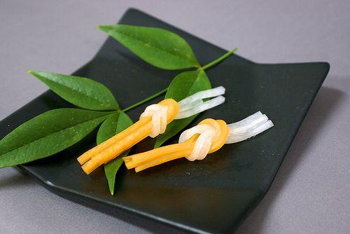 細く切った大根とにんじんが結んである、水引のような形と紅白が印象的な「あいおい結び」。おせちやお吸い物にちょこんと添えてあるとお正月っぽく、そしてお祝いのお料理という感じになります。大根とにんじんを細長く切ることができれば簡単に作れますよ!飾り切り「...