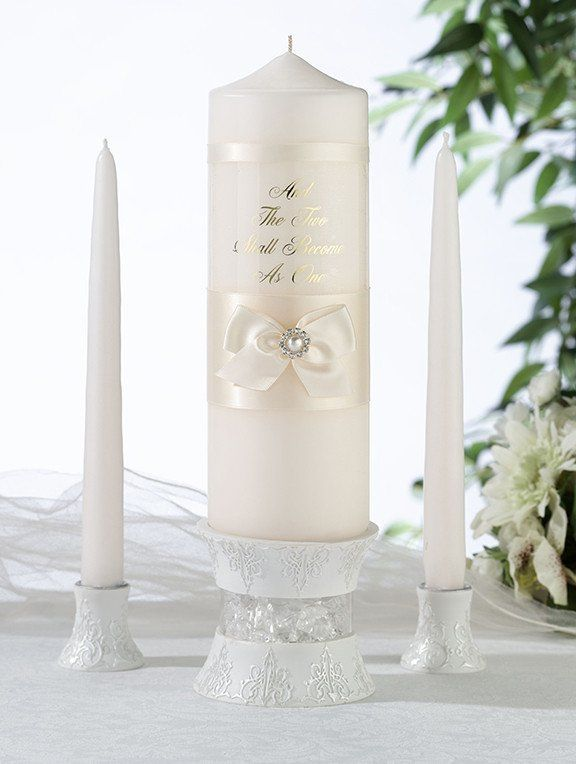 """This stunning Ivory pearl candle set is beautifully decorated with ivory satin bow and pearl. Pillar has the words """" And The Two Shall Become As One"""" Set includ"""