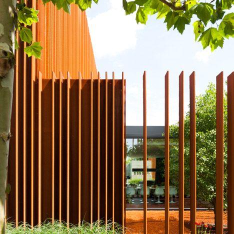 Strips of pre-rusted Corten steel run in vertical columns around this Belgian house.