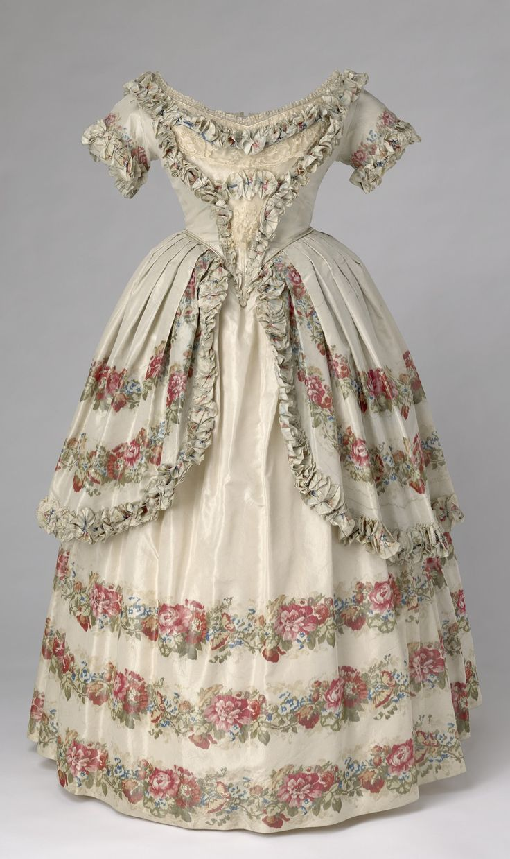 """Dress, 1851. Blue watered Spitalfields silk; round necked short sleved bodice decorated with lace on V shaped stomacher; full skirt with half overskirt edged with ruched ribbon; decorated with printed bands of roses and foliage. From the """"Victoria Revealed"""" exhibition at Kensington Palace. Royal Collection Trust/© Her Majesty Queen Elizabeth II 2016. CLICK FOR LARGER IMAGE."""