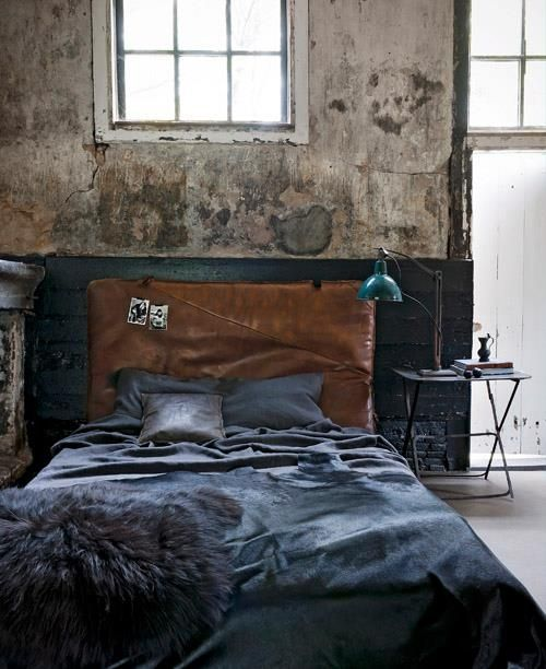 Tone on tone deep charcoals & indigos in the bedding, accentuated by a cowhide-brown headboard. Lots of texture, from the throw at the foot of the bed, to the headboard, to the plaster-washed walls. Industrial & spare (simple bedside table, unadorned windows), yet mysterious & cozy with the textures & dark bed linens.