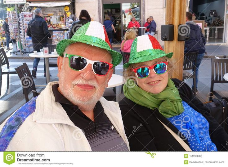 Photo about Civitavecchia Rome Italy a happy couple of elderly tourists sitting at a bar table wearing hats and glasses with the colors of Italian flag. Image of tourists, italy, elderly - 109760882